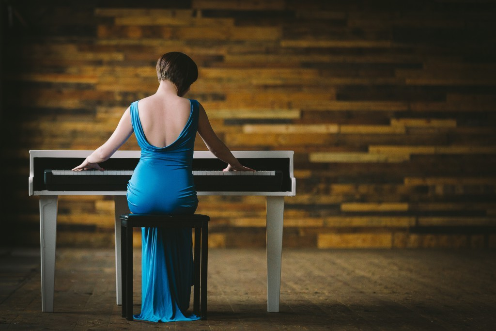 Liz Hendry wedding pianist sat at her white baby grand piano with a blue dress on